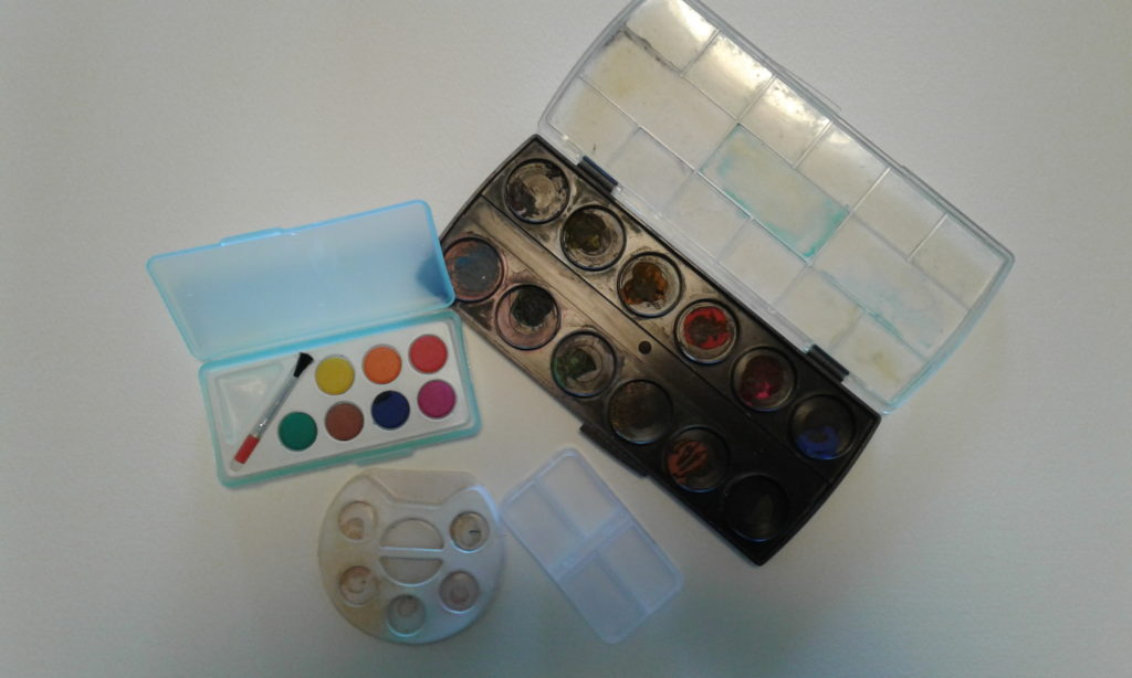 assorted children's paint palettes and pill box.